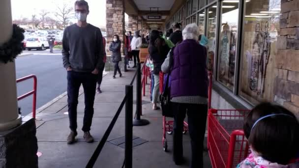 Rockville, MD, USA 11-29-2020: Customers wearing face masks due to COVID-19 are waiting in line doing social distancing before entering grocery store. Markets puts limitations to prevent overcrowding.