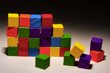 Colored wooden cubes wall ruined in dark background