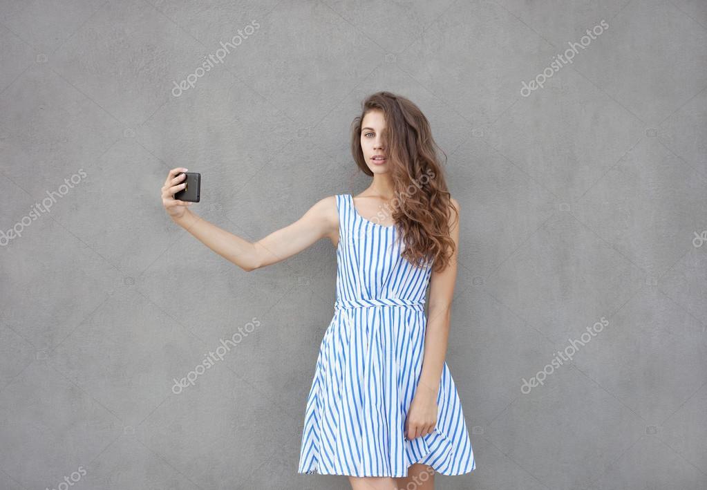 c8b169a80 Closeup retrato da jovem feliz sorridente mulher bonita luz vestido longo  morena cabelo cacheado posando contra a parede em um dia quente