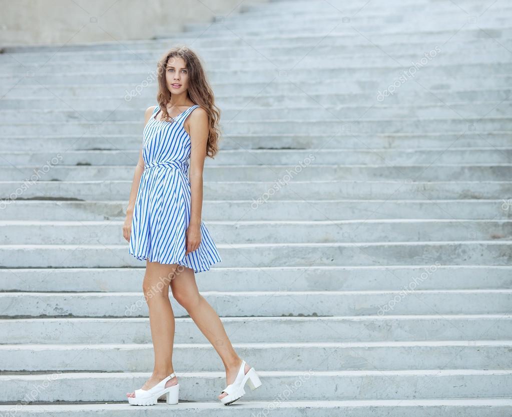 2205a1ed002e Χαρούμενος παιχνιδιάρης γυναίκα στο φως ριγέ άσπρο μπλε φόρεμα που ποζάρει  στο συγκεκριμένο κλιμακοστάσιο εξωτερική —