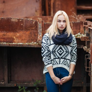 Young cute blonde woman in sweater, scarf, and jeans outdoors portrait with abandoned grunge background