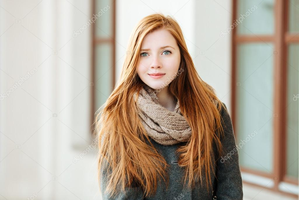 2b6fb03cd1a92 Young beautiful redhead woman wearing coat and scarf posing outdoors with  architectural background — Stock Photo
