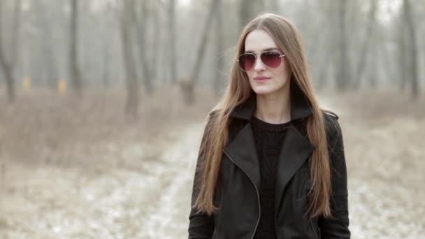 Fiatal gyönyörű nő divatos napszemüveg választ egy mozgatható telefon hív-ban tavaszi forest park