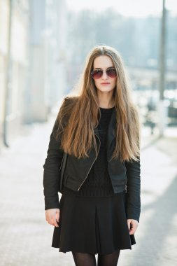 City portrait of young beautiful fashionable woman in sunglasses posibg outdoors at noon sun