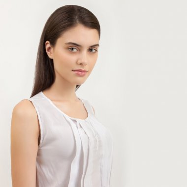 Portrait of young calm beautiful brunette woman posing for model tests against white background