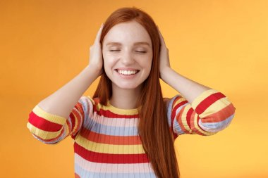 Dreamy charismatic relaxed tender redhead caucasian girl 20s close eyes cover ears imaging far away, smiling broadly enjoy silence peace comfort without sounds noise-free, orange background