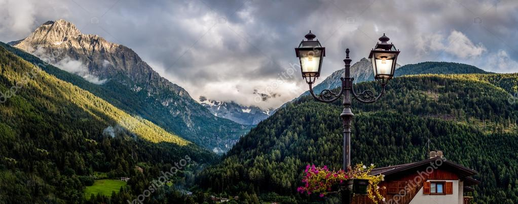 Lamp post in a mountain panorama with cloud and sun