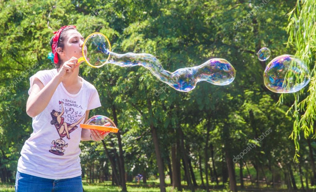 Happy young girl has fun with bubbles in a summer day