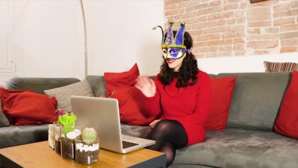 Mladá žena nosí benátské karneval masky konference volá na notebook nebo smartphone rozhovory s online rodinou nebo přáteli, pracuje z domova během pandemické karantény. Zdraví a koncepce strany