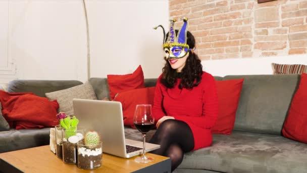 Junge Frau trägt venezianische Karnevalsmaske, telefoniert am Laptop mit Familie oder Freunden, arbeitet während der Pandemie-Quarantäne von zu Hause aus und klimpert mit Rotwein