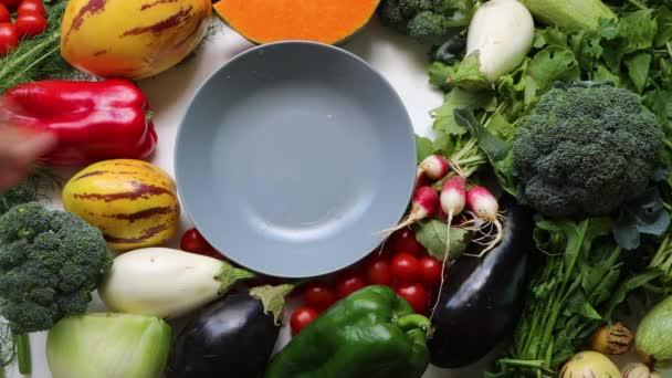 Mužská ruka uvedení šedé misky mezi zdravé jídlo čisté stravování výběr: ovoce, zelenina, papája, superfood, listová zelenina na bílém pozadí