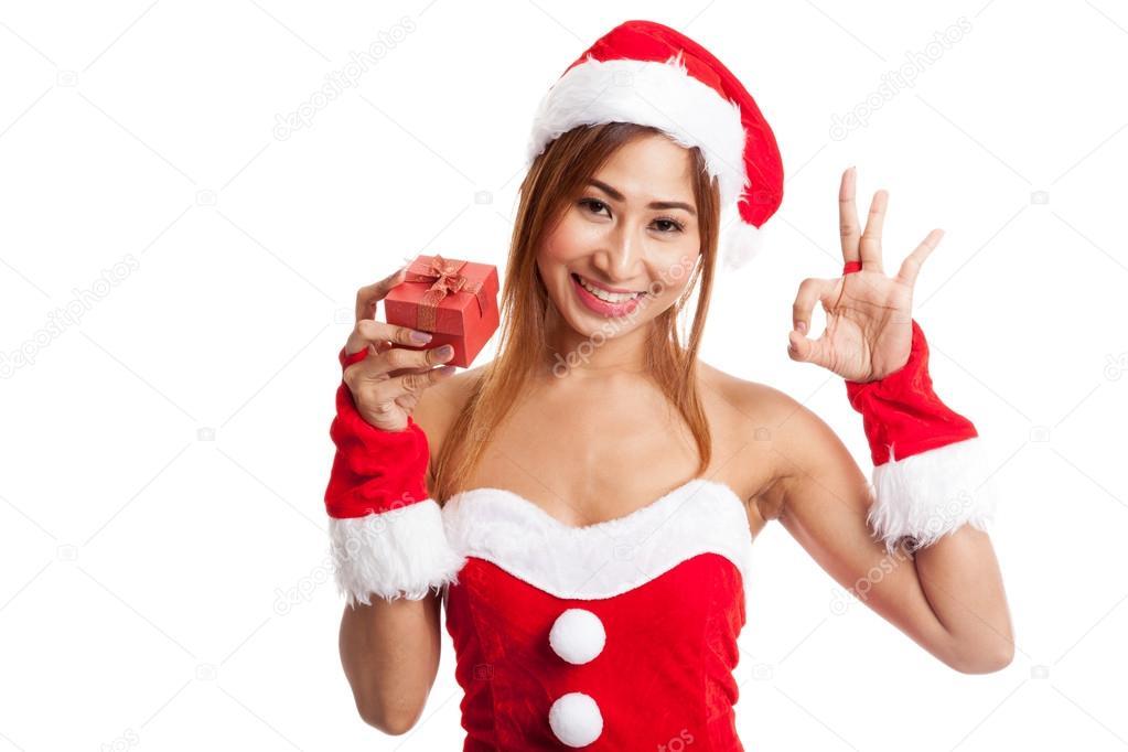 96148dcd96fc Ragazza asiatica di Natale show Ok con vestiti di Babbo Natale e  contenitore di regalo rosso isolato su priorità bassa bianca — Foto di ...