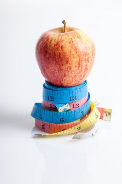 Red apple on four color measuring tapes