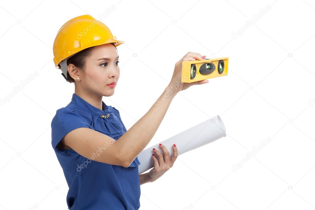 Asian engineer woman with blueprints and level