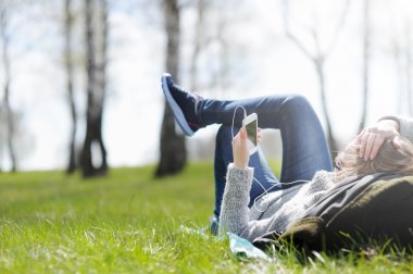 Young woman lying on grass in Park selecting music on smartphone