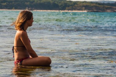 Girl meditating in the sea