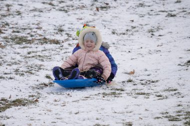 Friends and families are sledding down a large hill in a public park in Detroit
