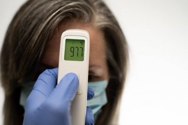 gloved hand holding a thermometer that displays 97.7 without a fever