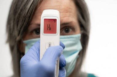 gloved hand holding a thermometer that displays HI in a red warning of a fever