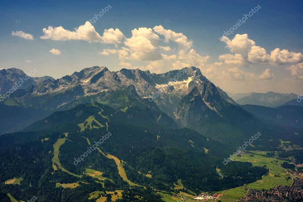 Фотообои Beautiful view at highest mountain peak Zugspitze and Alpspix with Garmisch Partenkirchen from Wank mountain. Hot summer day and amazing cloudy sky. Bavaria, Germany.