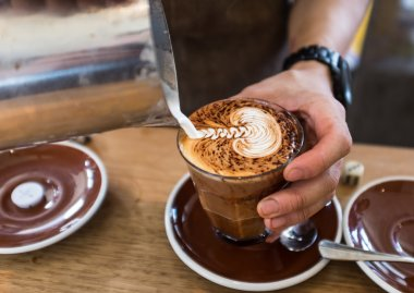 Barista pouring leaf pattern on a cappuccino coffee