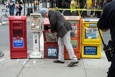 man purchasing newspaper from newspapers stand