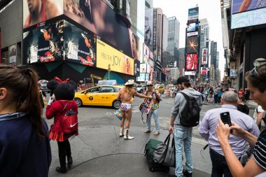 The naked cowboy of Times Square on day time.