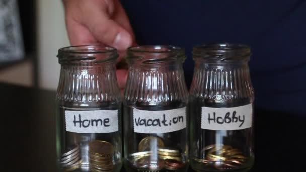 Člověk hodí minci v prasátko. Na sklenicích lepený bílými pruhy. Na proužky je napsáno, k jakému účelu že peníze budou směřovat.