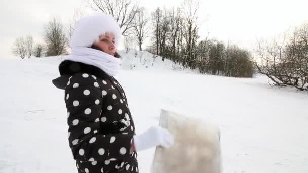 Das Mädchen erklimmt mit einem Schlitten einen schneebedeckten Hügel, um auf den Grund des Hügels zu fahren.