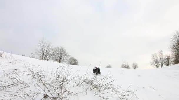 Das Mädchen sitzt auf einem Schlitten und rutscht einen verschneiten Hügel hinunter.