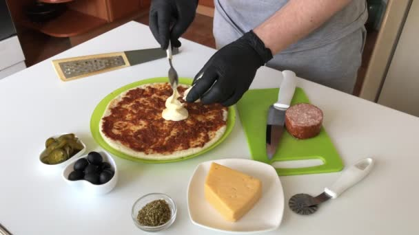 A man spreads mayonnaise on a base for a pizza smeared with tomato paste. Cooking ingredients are laid out nearby. Making pizza at home.