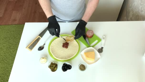 A man spreads tomato paste on a pizza base. Cooking ingredients are laid out nearby. Making pizza at home
