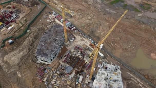Moderní rozvoj měst. Stavba s vícepodlažními budovami ve výstavbě. Stavební práce jsou v plném proudu. Let s otáčkou kamery. Letecká videografie