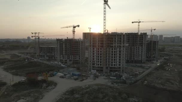Staveniště moderního městského bloku. Výškové budovy ve výstavbě. Jeřáby na staveništích. Letecká fotografie při západu slunce.