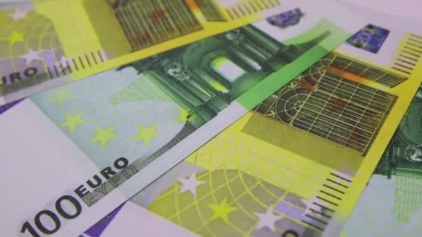 100 a 200 eurobankovek rotujících na stole. Rotace papírových peněz, detailní záběr