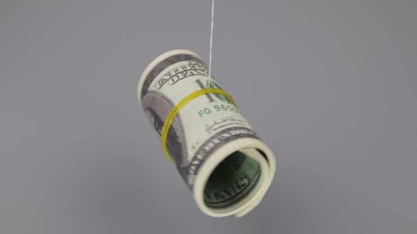 Zusammengerollte 100-Dollar-Banknoten drehen sich auf einem Faden auf grauem Hintergrund, Nahaufnahme