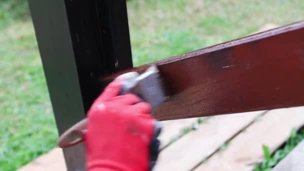 Frau in roten Arbeitshandschuhen übermalt ein hölzernes Geländer an der Quaste braun