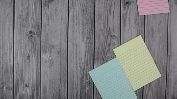 Colorful memo pads with matching notebooks and copyspace. Stop motion, top view