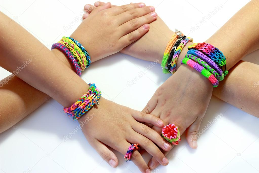 4 girl\'s hand with elastic and colorful rainbow loom bracelet on ...