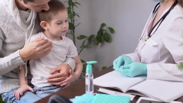 Eine junge Ärztin misst mit einem elektronischen Thermometer die Temperatur eines kleinen Jungen