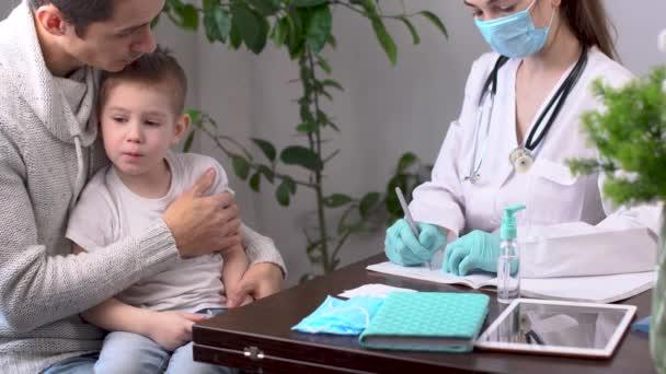 Ein kleiner Junge mit seinem Vater besucht die Kinderarztpraxis. Ein Arzt schreibt ein Rezept für ein krankes Kind