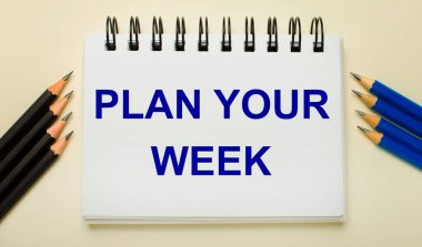 On a light background, a white notebook with the text PLAN YOUR WEEK and black and blue pencils on the sides.