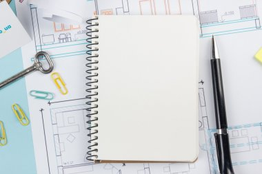 Real estate concept. Blank white notebook on architectural desk table blueprint background with key, pen, small house, office supplies. Copy space for ad text, top view.