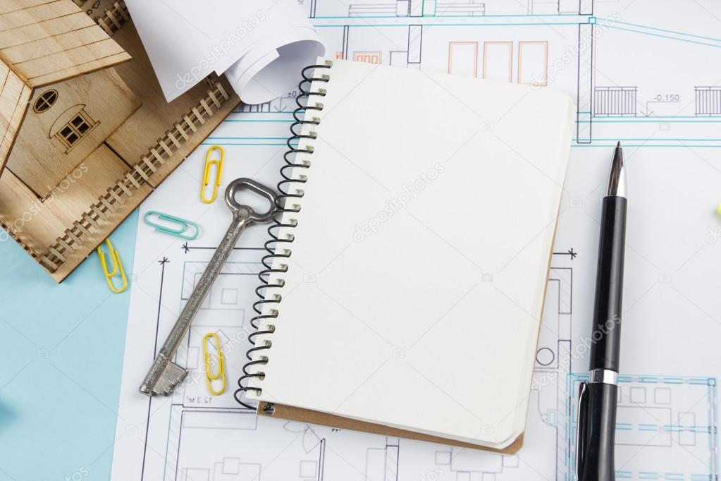 Real estate concept blank white notebook on architectural desk blank white notebook on architectural desk table blueprint background with key pen small house office supplies copy space for ad text top view foto malvernweather Image collections