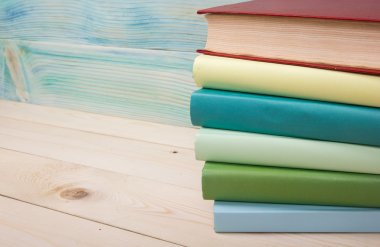 Back to school. Stack of colorful books on wooden table.