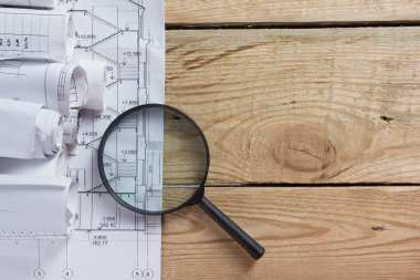 Architectural project, blueprints, blueprint rolls near checkered blank paper with pen on vintage wooden background. Construction concept. Architect workplace top view. Copy space