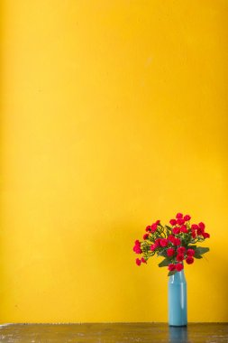 Red flowers in vase on yellow wall background. Old boards with flowers vintage concept