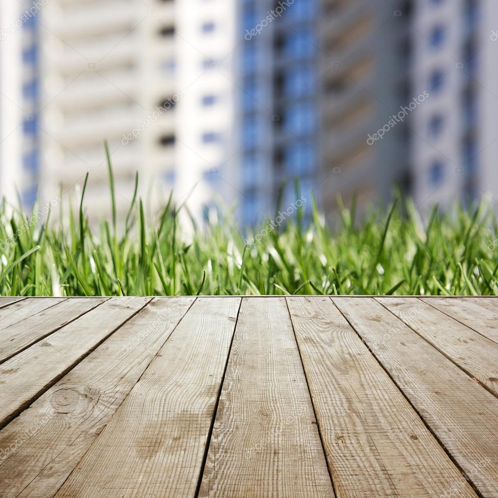Wooden perspective floor with planks on blurred grass real estate