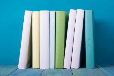 Row of colorful books, grungy blue background, free copy space