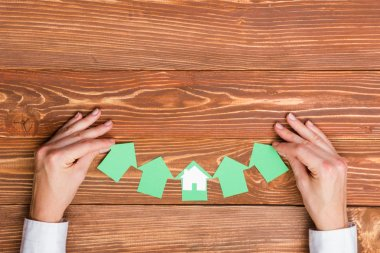 Hands holding green paper house figure models arrows on white background. Concept for comparision of real estate houses pricing Real Estate Concept. Top view, copy space. Eco house